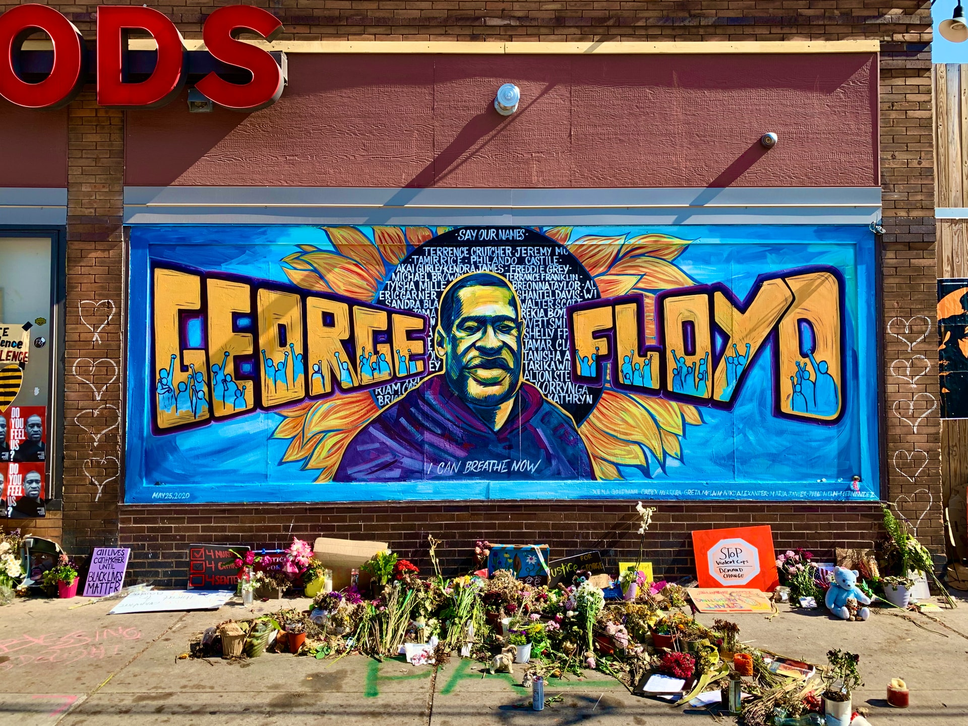 mural in Minneapolis of George Floyd with flowers and BLM signs on the sidewalk